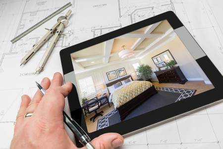 master bedroom: Hand of Architect on Computer Tablet Showing Custom Master Bedroom Over House Plans, Compass and Ruler.