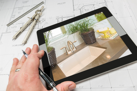 estate planning: Hand of Architect on Computer Tablet Showing Luxury Bathroom Details Over House Plans, Compass and Ruler.