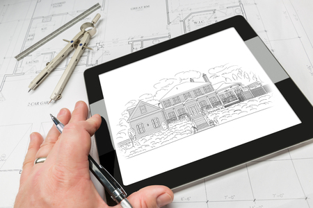 construction projects: Hand of Architect on Computer Tablet Showing Home Illustration Over House Plans, Compass and Ruler.