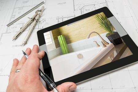 Mano del arquitecto en la tableta de la computadora que muestra detalles de baño de lujo sobre los planos de la casa, la brújula y la regla. Foto de archivo