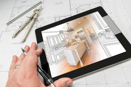 planning: Hand of Architect on Computer Tablet Showing Custom Kitchen Illustration Photo Combination Over House Plans, Compass and Ruler. Stock Photo