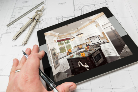 architect tools: Hand of Architect on Computer Tablet Showing Custom Kitchen Photo Over House Plans, Compass and Ruler. Stock Photo