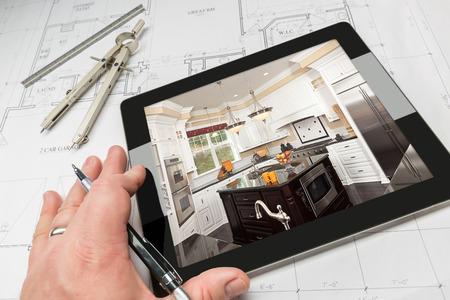 Mano di Architetto sul Tablet computer che mostra cucina Photo sui piani Custom House, riga e compasso.