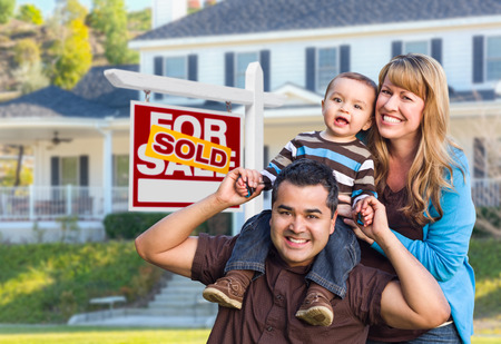 家庭: 快樂混血年輕家庭出售家門前出售房地產標誌和房子。 版權商用圖片