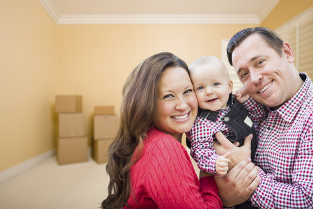family  room: Happy Young Family In Room With Moving Boxes.