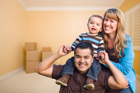 Happy Young Mixed Race Family In Room With Moving Boxes.