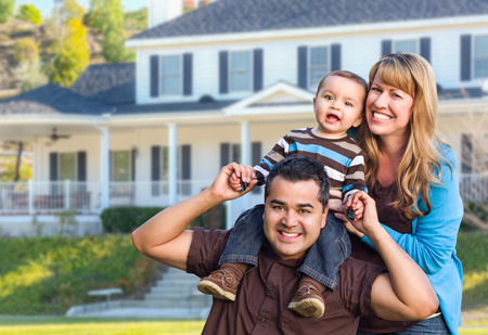 Happy Mixed Race Young Family in Front Yard of Beautiful House.
