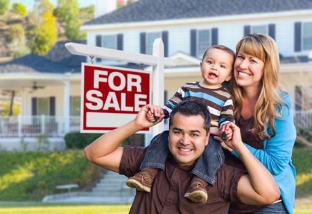 family outside: Happy Young Mixed Race Family in Front of For Sale Real Estate Sign and New House.