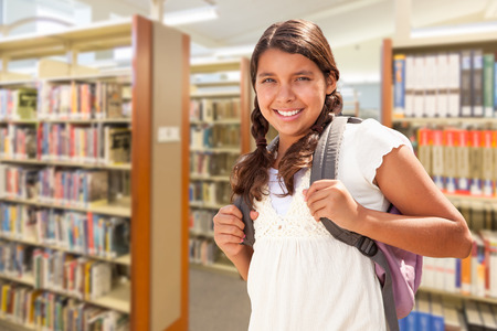 Happy Hispanic Girl Student Wearing Backpack Walking in the Library. Stock Photo