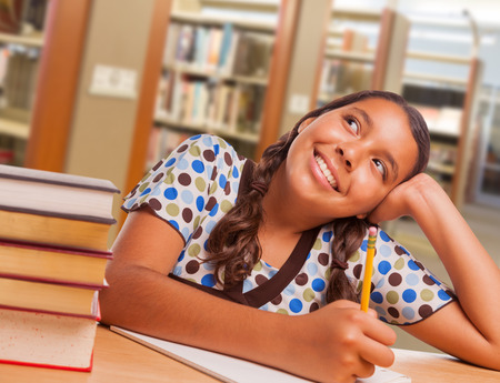 Happy Hispanic Girl Student with Pencil and Books Daydreaming While Studying in Library. photo