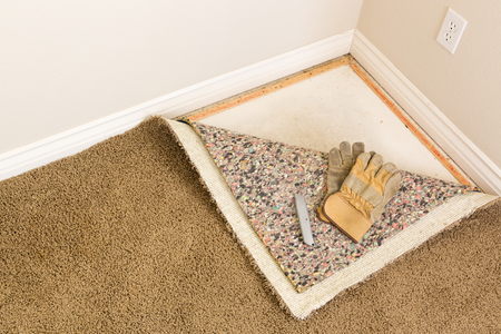 Construction Gloves and Utility Knife On Pulled Back Carpet and Pad In Room.