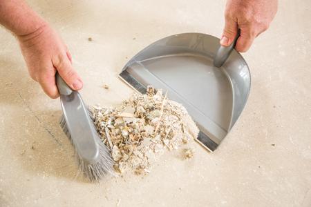 Werknemer oppakken stapel puin op Cement met penseel en stof Pan. Stockfoto
