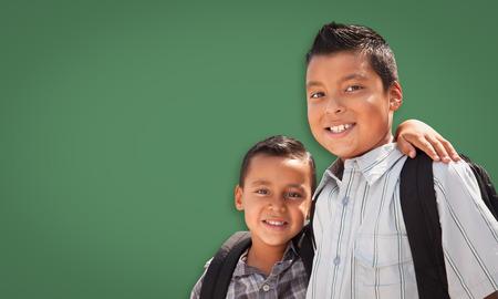 Cute Hispanic Boys Wearing Backpacks In Front of Blank Chalk Board. photo