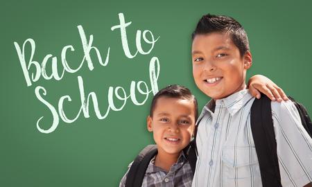 Cute Hispanic Boys Wearing Backpacks In Front of Back To School Written On Chalk Board. photo