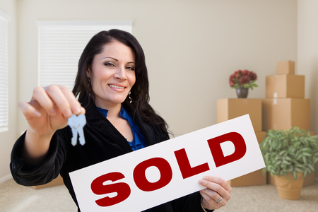 Happy Hispanic Female Real Estate Agent with Sold Sign and Keys in Room with Moving Boxes. photo