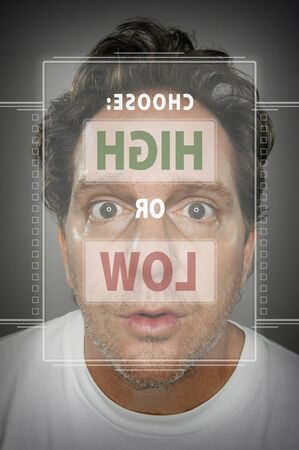Dumbfounded Looking Man In Front of Touch Screen Deciding on High or Low. Stock Photo