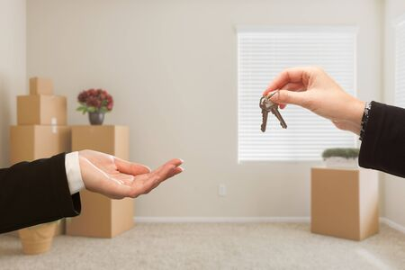 over packed: Woman Handing Over House Keys In Room with Packed Moving Boxes.