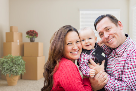 family  room: Happy Caucasian Family with Baby In Room with Moving Boxes. Stock Photo