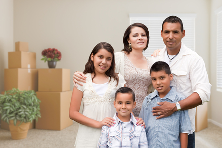 Happy Hispanic Family in Empty Room with Packed Moving Boxes and Potted Plants. photo