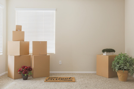 Variety of Packed Moving Boxes and Potted Plants and Welcome Mat In Empty Room with Room For Text. Stock Photo