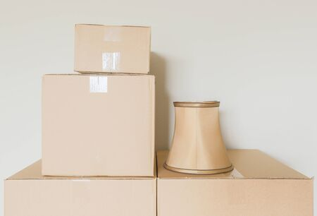lamp shade: Variety of Packed Moving Boxes and Lamp Shade In Empty Room Against Wall. Stock Photo