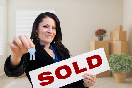 real estate sold: Happy Hispanic Female Real Estate Agent with Sold Sign and Keys in Room with Moving Boxes. Stock Photo