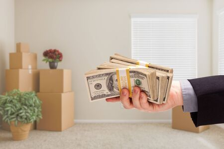 over packed: Man Handing Over Cash In Room with Packed Moving Boxes.