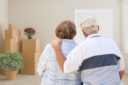Senior Couple Facing Empty Room with Packed Moving Boxes and Potted Plants.