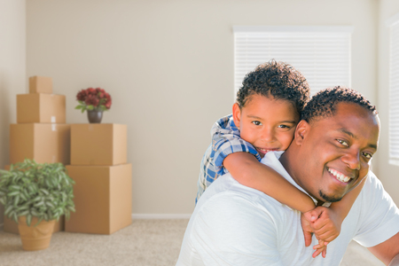 Happy Mixed Race African American Father and Son In Room with Packed Moving Boxes. Stock Photo