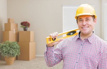 worker man: Happy Male Construction Worker In Room With Moving Boxes Holding Level.