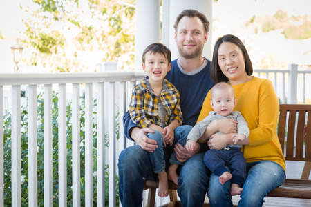 front porch: Young Mixed Race Chinese and Caucasian Family Portrait On Their Front Porch.