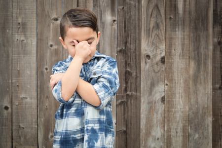 Young Frustrated Mixed Race Boy With Hand on Face Against Wooden Fence.