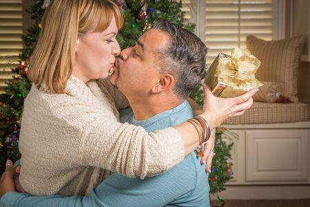 mixed race: Happy Young Mixed Race Couple with Present Near Christmas Tree.