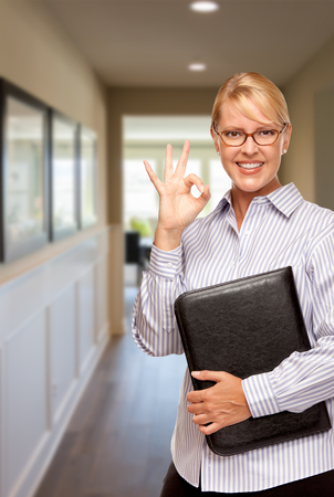 Smiling Businesswoman with Folder and Okay Hand Sign In Hallway of House. Reklamní fotografie - 69323939