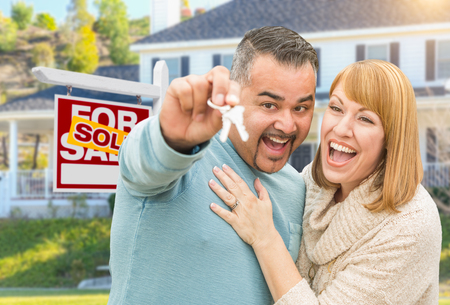 buyer: Happy Mixed Race Couple With Keys in Front of Sold For Sale Real Estate Sign and New House. Stock Photo