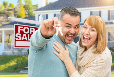 purchase: Happy Mixed Race Couple With Keys in Front of For Sale Real Estate Sign and New House.