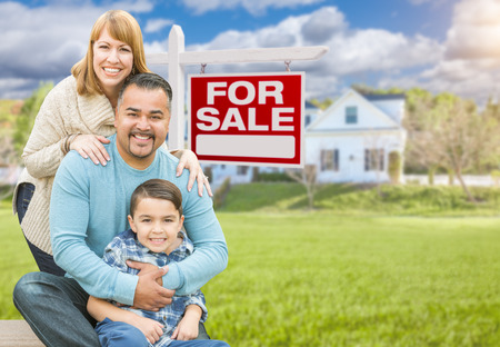 real estate sold: Happy Mixed Race Hispanic and Caucasian Family Portrait In Front of House and Sold For Sale Real Estate Sign.