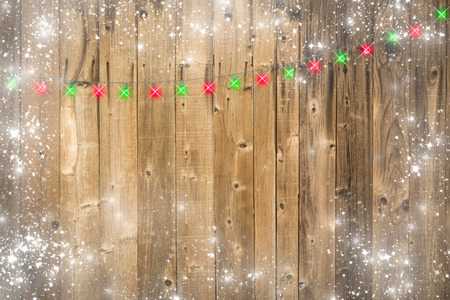 lustrous: Lustrous Wooden Background with Bright Green and Red Christmas Lights and Snowy Border.