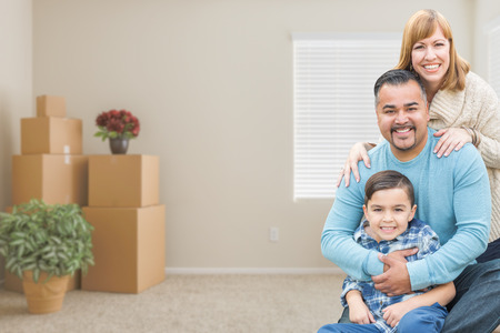 mixed family: Happy Mixed Race Family with Son in Room with Packed Moving Boxes. Stock Photo