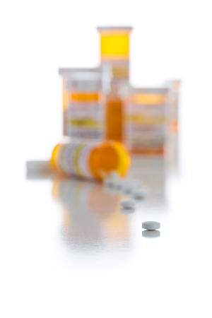 prescription medicine: Non-Proprietary Medicine Prescription Bottles and Spilled Pills Isolated on a White Background. Stock Photo