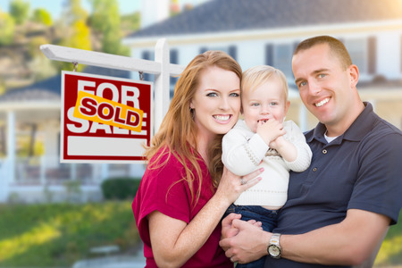 first home: Happy Young Military Family in Front of Sold For Sale Real Estate Sign and New House.