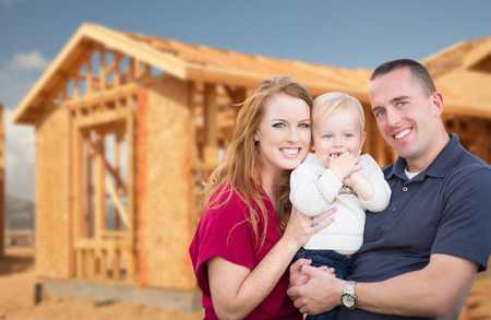 Happy Young Military Family Outside Their New Home Framing at the Construction Site. Archivio Fotografico