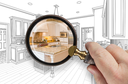 residences: Hand Holding Magnifying Glass Revealing Custom Kitchen Design Drawing and Photo Combination.