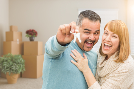 Mixed Race Couple Holding House Keys Inside Empty Room with Moving Boxes.