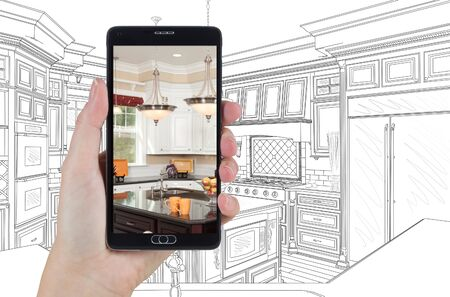holding smart phone: Hand Holding Smart Phone Displaying Photo of Custom Kitchen Drawing Behind.
