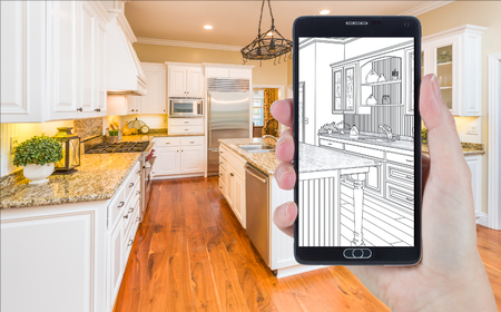 holding smart phone: Hand Holding Smart Phone Displaying Drawing of Custom Kitchen Photo Behind.