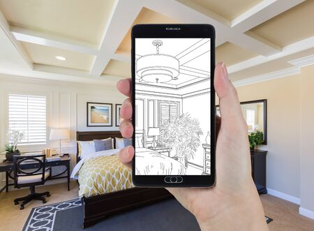 holding smart phone: Hand Holding Smart Phone Displaying Drawing of Custom Bedroom Photo Behind.
