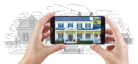 holding smart phone: Hands Holding Smart Phone Displaying Custom Home Photo of Drawing Behind.
