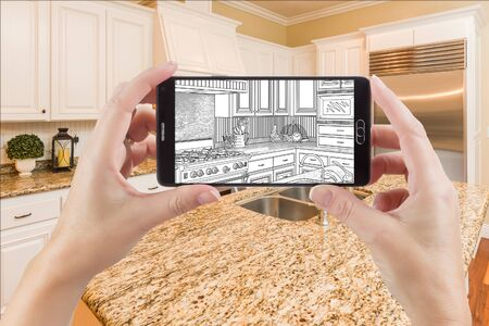 holding smart phone: Hands Holding Smart Phone Displaying Drawing of Custom Kitchen Photo Behind.