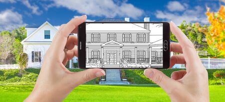 holding smart phone: Hands Holding Smart Phone Displaying Drawing of Custom Home Photo Behind. Stock Photo